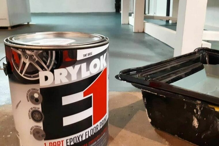 A can of DRYLOK® Epoxy is set next to a paint tray. The floor is tan and teal, with some white structure also pictured.